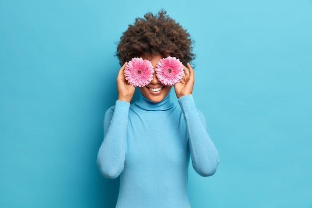 La giovane donna afroamericana soddisfatta con i capelli ricci copre gli occhi con sorrisi di gerbere rosa delicatamente vuole fare bouquet di fiori preferiti