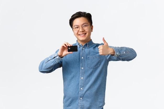 Довольный молодой азиатский предприниматель мужского пола, открывающий собственный стартап, открывает банковский счет, показывая палец вверх в ...