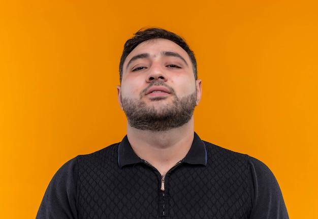 Giovane uomo barbuto soddisfatto in camicia nera che guarda l'obbiettivo con un sorriso sicuro sul viso