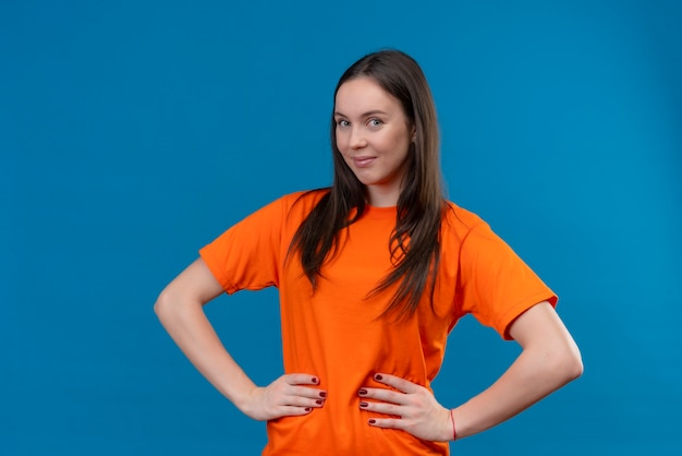Satisfied young beautiful girl wearing orange t-shirt looking at camera with confident smile on face standing over isolated blue background