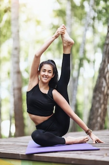 Satisfied young brunette woman in black sportswear practices yoga doing surya yantrasana exercise sitting in a compass pose on a wooden bridge in the park