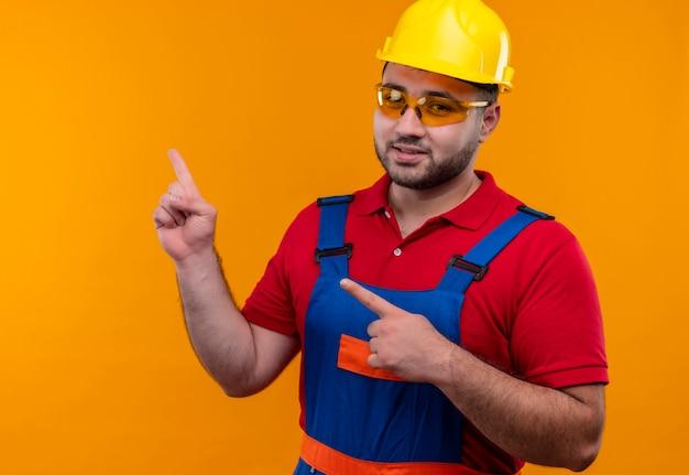 建設ユニフォームと安全ヘルメットで満足している若いビルダーの男は、横に指で自信を持って指しているように見えます