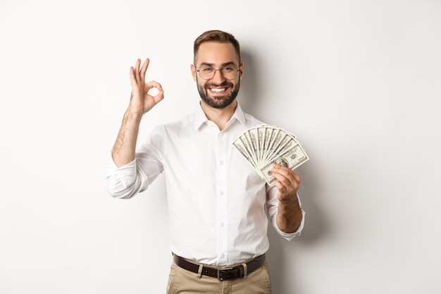 Satisfied young businessman showing money, make okay sign, earning cash, standing over white background.