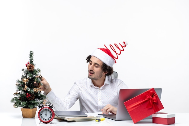Довольный молодой бизнесмен с забавной шляпой санта-клауса, украшающей елку и празднующей рождество в офисе на белом фоне