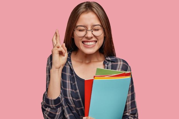 Довольный молодой предприниматель позирует на розовой стене в очках