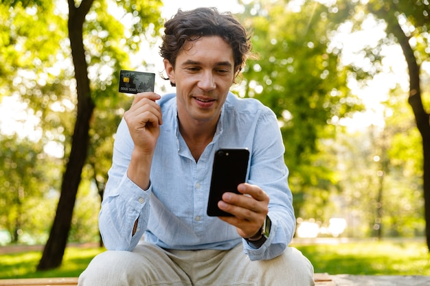 Satisfied young casual man holding mobile phone