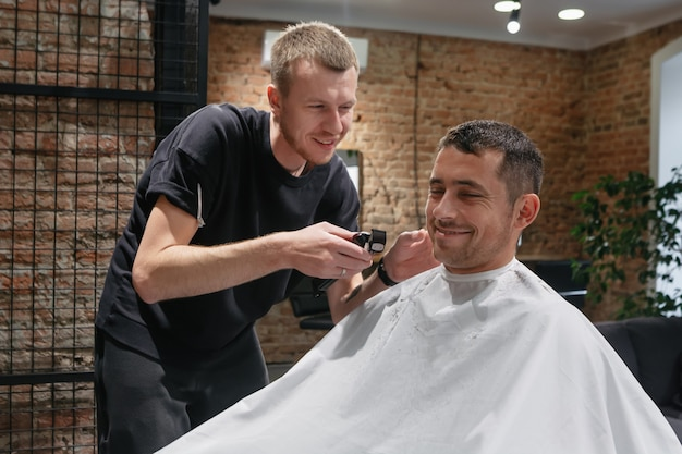 Satisfied young caucasian man doing hairstyle in barbershop.