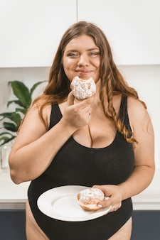 Satisfied young fat woman eating a cake happy smiling wearing black swimsuit. beautiful chubby young woman eating unhealthy food.