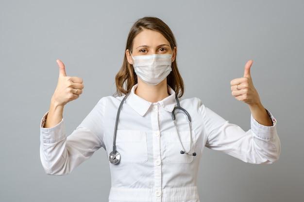 Удовлетворенная молодая женщина-врач показывает палец вверх жест изолированы