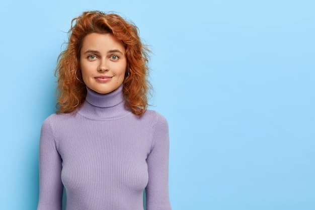 건강한 피부, 빨간 머리를 가진 만족스러운 젊은 여성 모델, 단호하게 보이고, 대담을 듣고, 캐주얼 한 이야기를 듣고, 파란색 벽에 고립 된 보라색 터틀넥을 착용하고, 공간 영역을 옆으로 복사