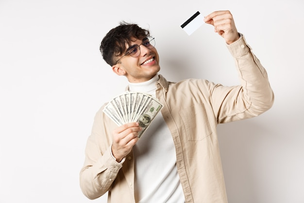 Satisfied young guy holding money looking pleased and smiling at plastic credit card choose contactl...