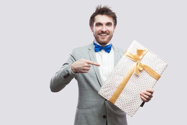 Удовлетворенный молодой человек в классическом сером пальто и синем галстуке-бабочке стоит и показывает пальцем, чтобы представить с желтым бантом и зубастой улыбкой, глядя в камеру. крытый, изолированный, студийный снимок, серый фон