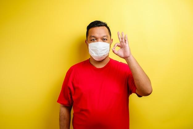 黄色の背景に対して大丈夫サインを示す医療マスクで満足している若い男