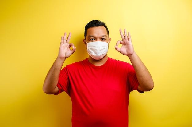 黄色の背景に対して大丈夫サインを示す医療マスクで満足している若い男 Premium写真