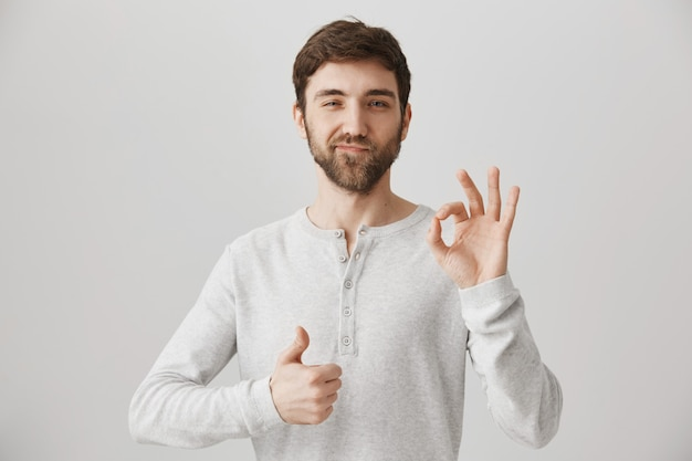 Satisfied young man show thumbs-up and okay sign