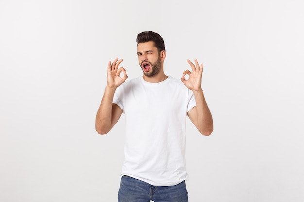 Satisfied young man showing okay sign isolated on white.