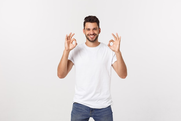 Satisfied young man showing okay sign isolated.