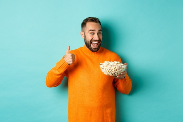 Satisfied young man, showing thumb-up and smiling, eating popcorn and watching good movie or tv, standing over blue background.