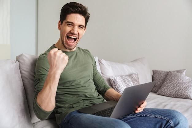Довольный молодой человек, используя портативный компьютер
