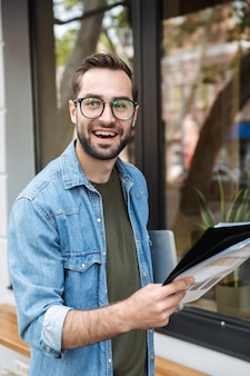 Satisfied young man wearing eyeglasses reading newspaper while walking through city street with laptop in hand