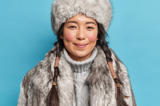 Soddisfatta giovane donna siberia con due trecce guance rosee sorride piacevolmente davanti a abiti per condizioni climatiche polari fredde isolate su muro blu