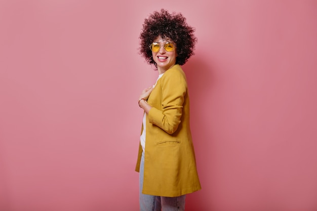 Satisfied young smiling girl with curls wearing yellow jacket looking at front over pink wall