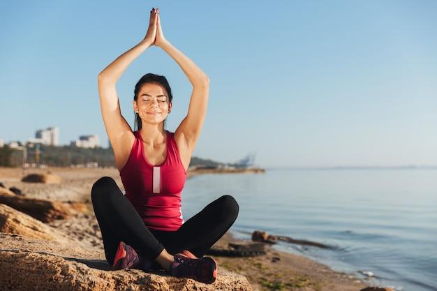 Довольная молодая спортсменка, сидящая в позе йоги