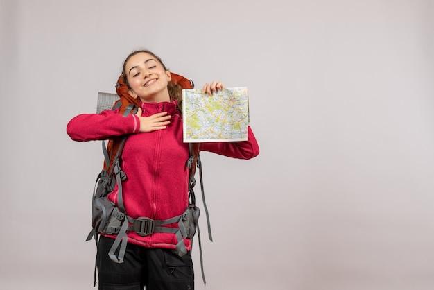 Довольный молодой путешественник с большим рюкзаком держит карту на сером