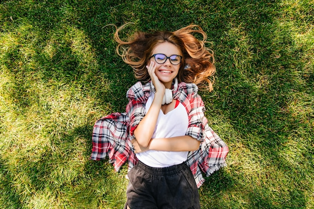 Satisfied young woman expressing happiness in park. overhead portrait of lovely girl lying on green grass.