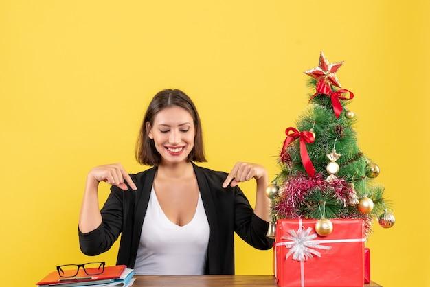 노란색 사무실에서 장식 된 크리스마스 트리 근처 소송에서 아래쪽을 가리키는 만족 된 젊은 여자
