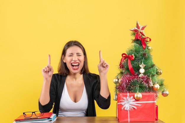 노란색에 사무실에서 장식 된 크리스마스 트리 근처 소송에서 가리키는 만족 된 젊은 여자
