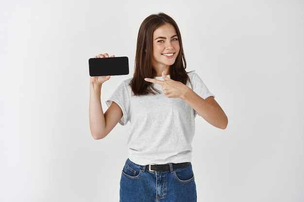 Satisfied young woman showing smartphone blank screen, pointing at mobile display and smiling, recommending application or shopping site, white wall.