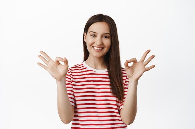 Довольная молодая женщина показывает «окей ноль», подписывает «ок» и кивает в знак одобрения, хвалит хороший выбор, делает вам комплимент, соглашается и любит что-то хорошее, белая стена.
