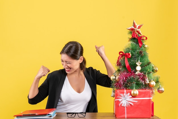Satisfied young woman in suit near decorated christmas tree at office on yellow