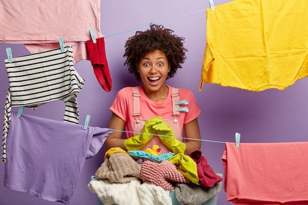 Giovane donna soddisfatta con un afro che posa con la lavanderia in tuta
