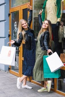 Satisfied young women holding shopping bags posing in front of clothes store