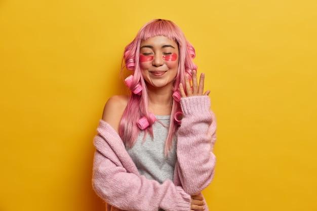 Donna sorridente soddisfatta con i capelli rosa, applica rulli e assorbenti di bellezza, vestita con un maglione roseo, gode del tempo libero da spendere per se stessa