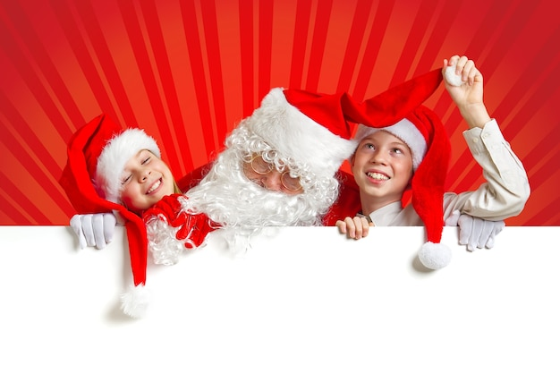 Satna claus with funny children in red christmas gnome hats peeking out from behind a blank white ba...