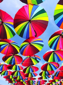 Saturated colorful umbrellas against the blue sky hang overhead