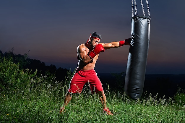 Saturated shot of a male boxer training with sandbag