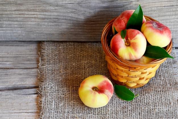 Свежие органические китайские плоские персики с листьями в корзине. пончик saturn, персик донута, paraguayo. здоровая концепция еды или диеты. селективный фокус.