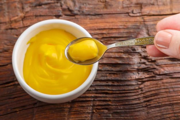 Соусники с сырным соусом и рука с соусом в ложке на деревянном столе