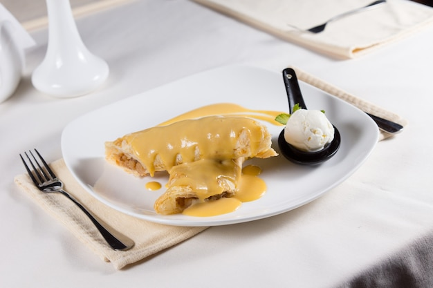 Sauce covered gourmet dessert crepes with scoop of ice cream served on white plate in restaurant