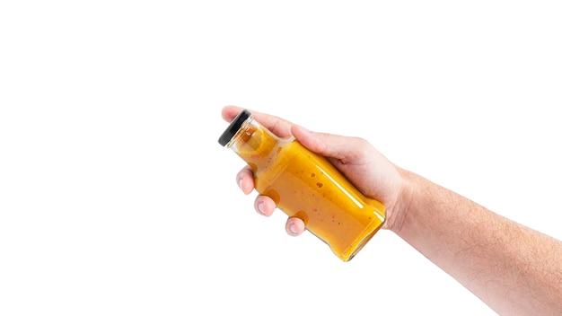 Соус в бутылке, изолированные на белом фоне. бутылка в руке. фото высокого качества