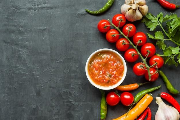 Соус, кетчуп, лечо в тарелке. чили помидоры черри чеснок и другие специи на черном