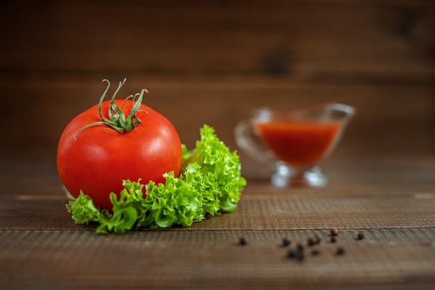 Соус, салат и помидоры на деревянном. здоровое питание и вегетарианство.