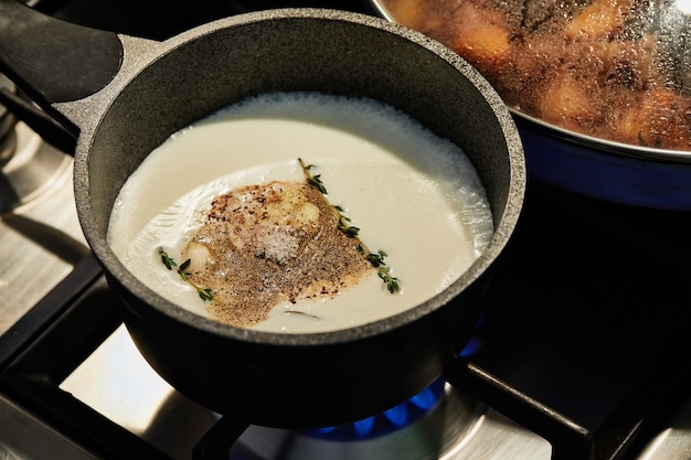 Sauce with herbs and thyme sprigs is cooked in saucepan on gas oven.