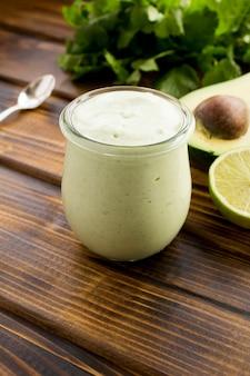 Соус с йогуртом, авокадо, лаймом и кинзой на коричневом деревянном столе. крупный план.