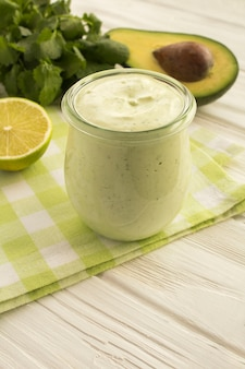 Соус с йогуртом, авокадо, лаймом и кинзой на белом деревянном фоне. расположение вертикальное.