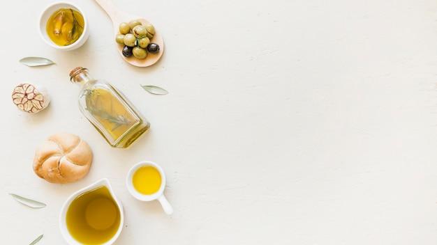 Bottiglia di sauceboats con olive da olio e prodotti da forno